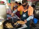 Этот парень в модных очках готовит китайское блюдо Char Koay Teow. О-в Пинанг. Малайзия