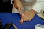 Эбе разрезает рыбу со стороны хребта