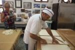 Пекарь разрезает полосы фило на квадраты