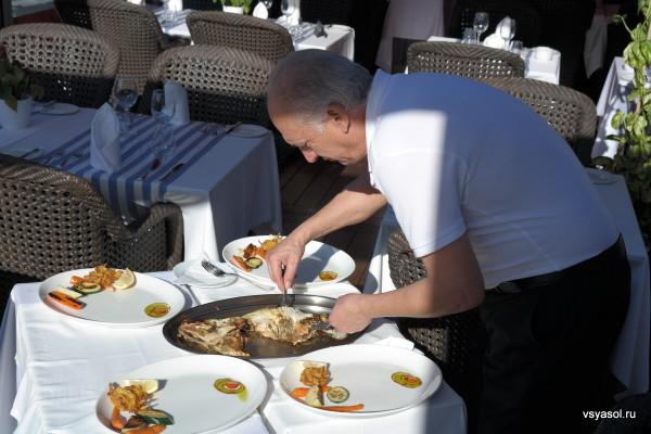Хозяин ресторана Эль Фаро в порту Адриано разделывает рыбу-петуха