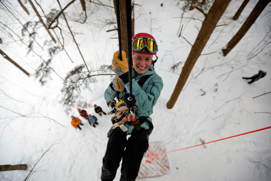 Image of woman rappelling in the woods in winter at Arbortrek at Smuggler's Notch