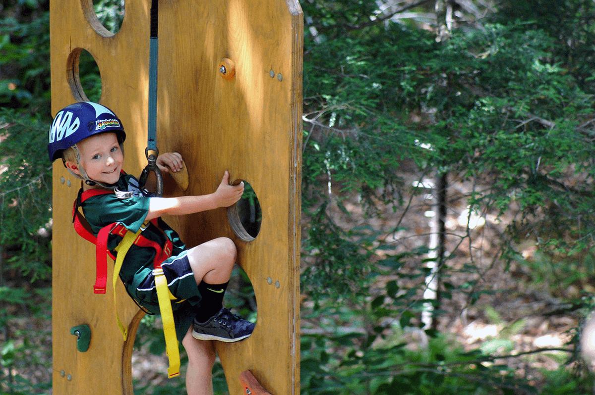 Image of boy climbing an outdoor wall at Arbortrek at Smuggler's Notch