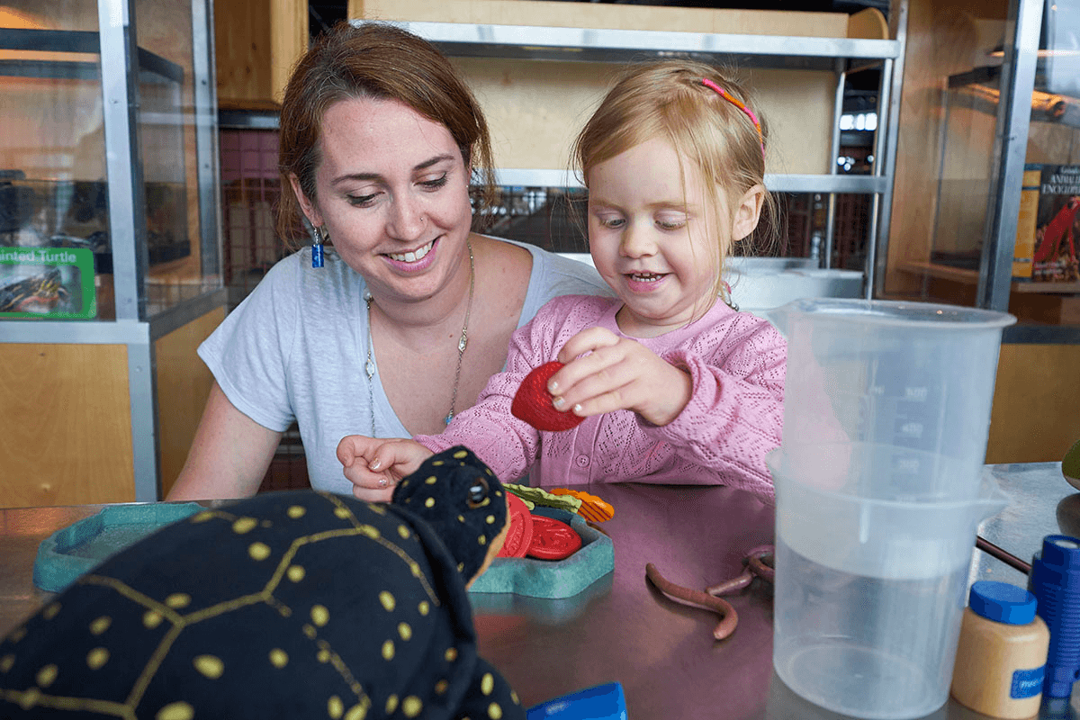 Image of mother and young daughter playing with toys