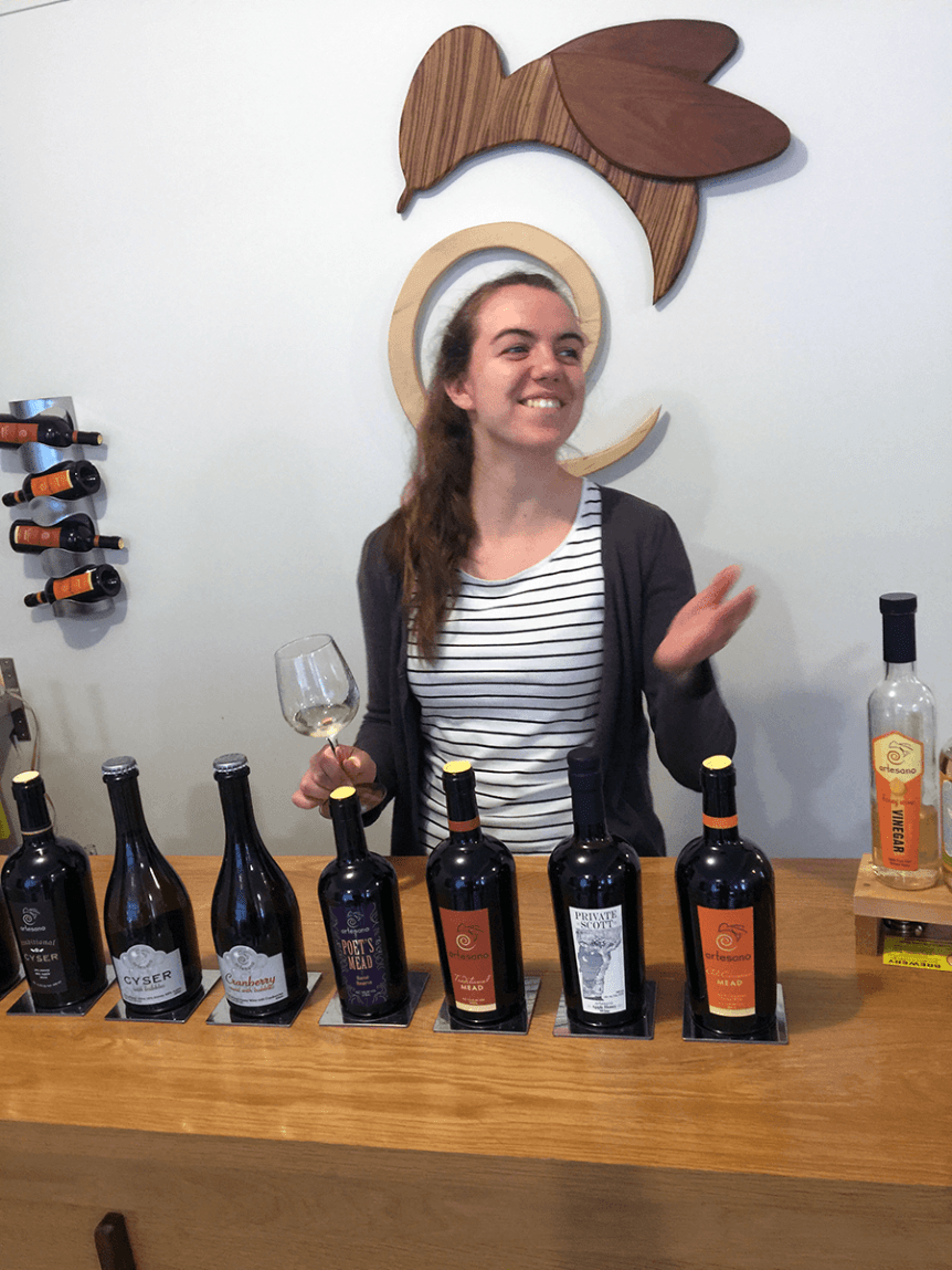 Image of a woman holding a glass of mead at Artesano Meadery