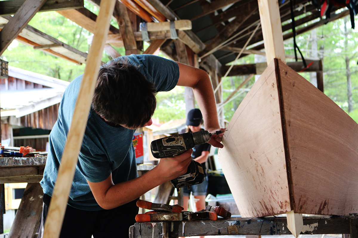 image of a boy building a boat