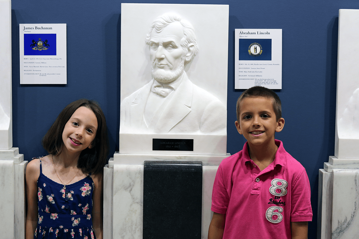 Image of 2 children standing in front of an engraving of Abraham Lincoln