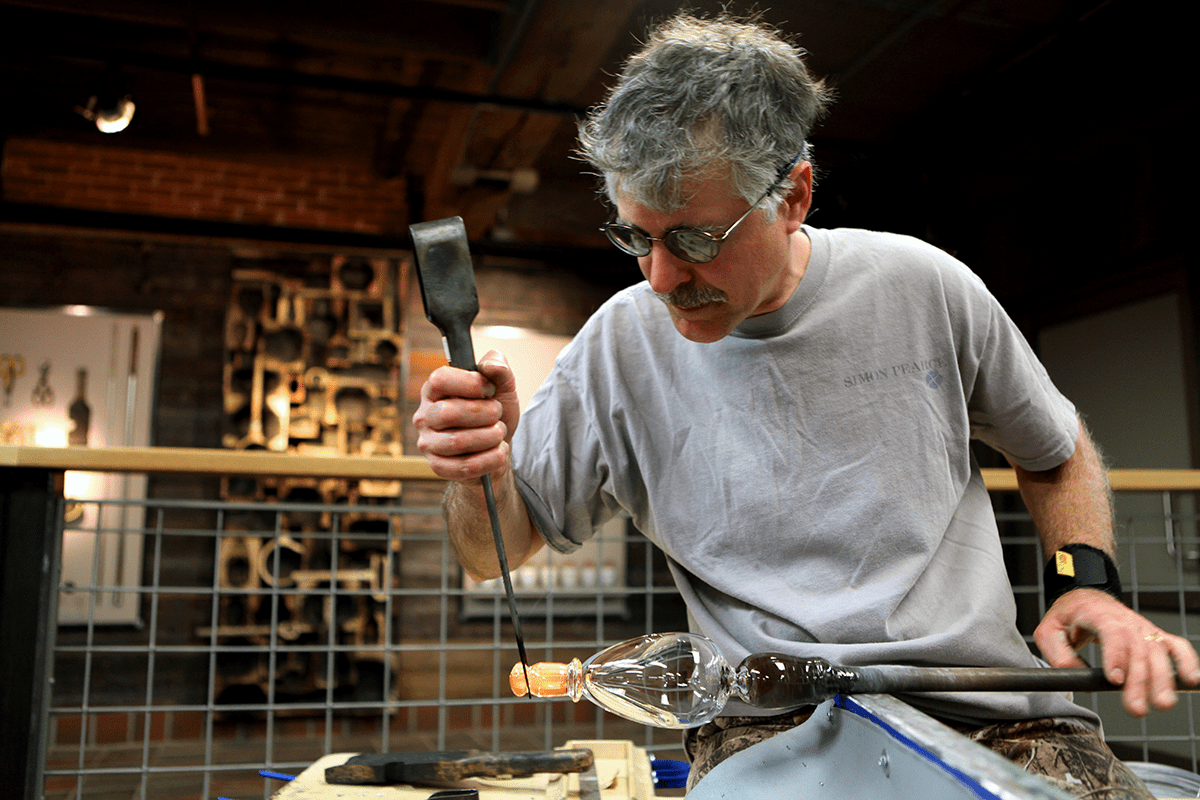 Image of a gaffer working a piece of hot glass at Simon Pearce