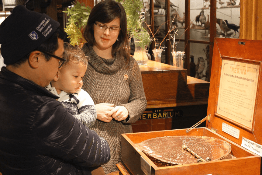 Image of family looking at antique music box at Fairbanks Museum