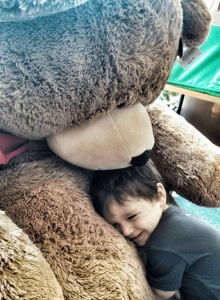 Image of a young boy hugging a large overstuffed teddy bear at Vermont Teddy Bear Company