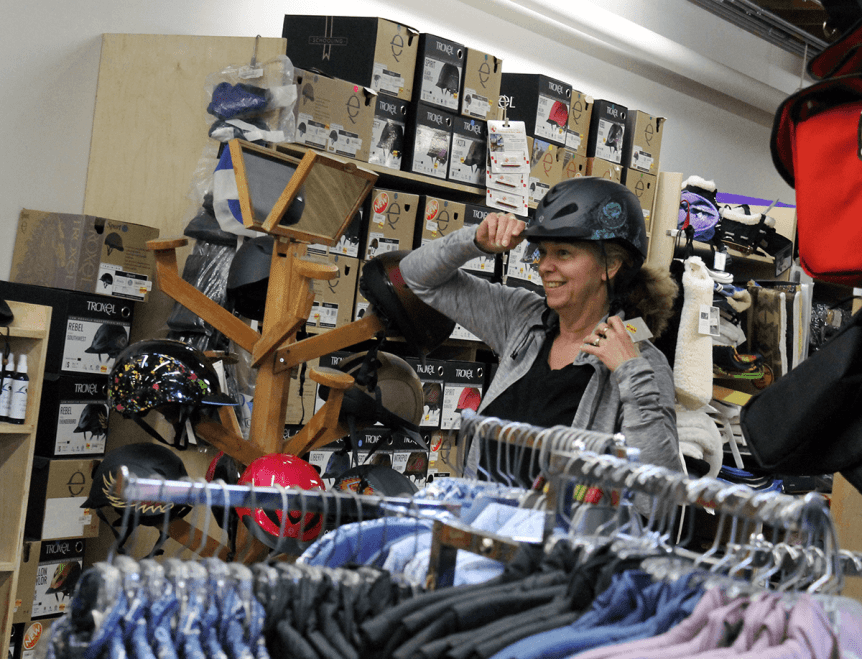 Image of woman trying on bike helmets at Farm-Way