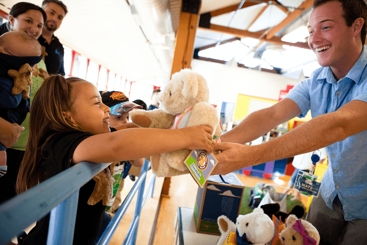 Image of girl receiving a Vermont Teddy Bear Giving Bear