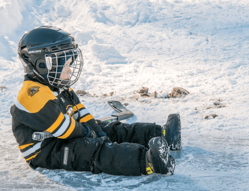 Image of a little boy sitting on the ice holding a hockey stick at Lake Morey Resort