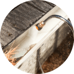 Rounded gutter cleaning tool blasts pine needles and dirt from gutter in Burlington, VT