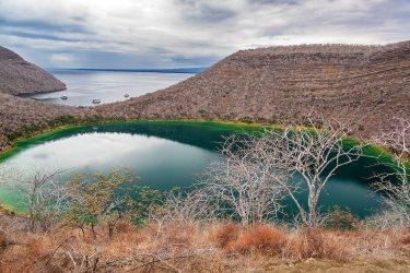 Laguna salobre en la isla Isabela en las Islas Galápagos en Ecuador con en el fondo el Océano Pacífico .