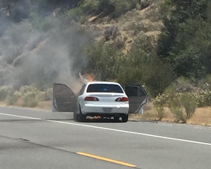 A white Toyota Corolla along Highway 138 caught fire and the flames quickly spread into the vegetation. Photo taken by Eddie Moreno)