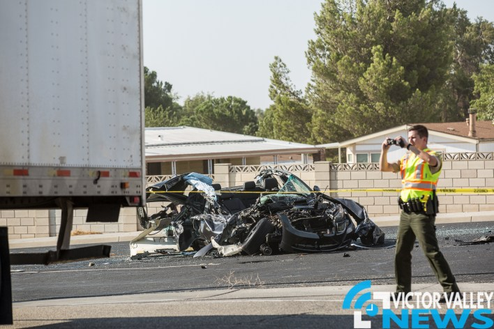 A Victorville Deputy photographs the rear of the semi where the BMW struck. (Gabriel D. Espinoza, Victor Valley News)