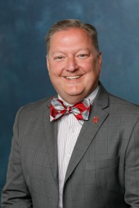 Person with fair complexion, dressed in grey suit coat, with grey windowpane stripes, a red O (Ohio State) lapel pin, white shirt with grey stripes and bowtie with large red and grey angled diamond shapes