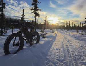 Fat Tire bike on a winter trail in willow alaska with sunset behind it.