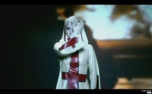 Symbols of dark forces now proliferate throughout the entertainment industry. Here a pop star is covered in upside down crucifixes.