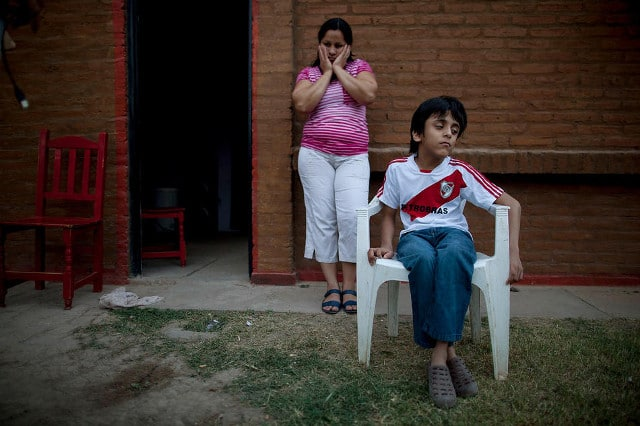 Silvia Alvarez leans against her home while keeping an eye on her son, Ezequiel Moreno, who was born with hydrocephalus, in Gancedo, in Chaco province, Argentina, April 1, 2013. Chaco provincial birth reports show that congenital defects quadrupled in the decade after GM crops arrived. CREDIT: Natacha Pisarenko/AP