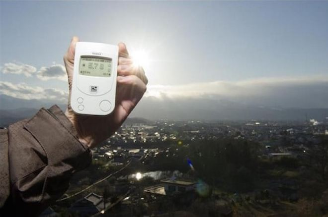 "A Greenpeace team member holding a Geiger counter displaying radiation levels of 5.78 microsievert per hour outside Fukushima city on March 27, 2011. Radiation levels far exceed exposure limits considered ""safe"" for the 400,000 strong human population below."
