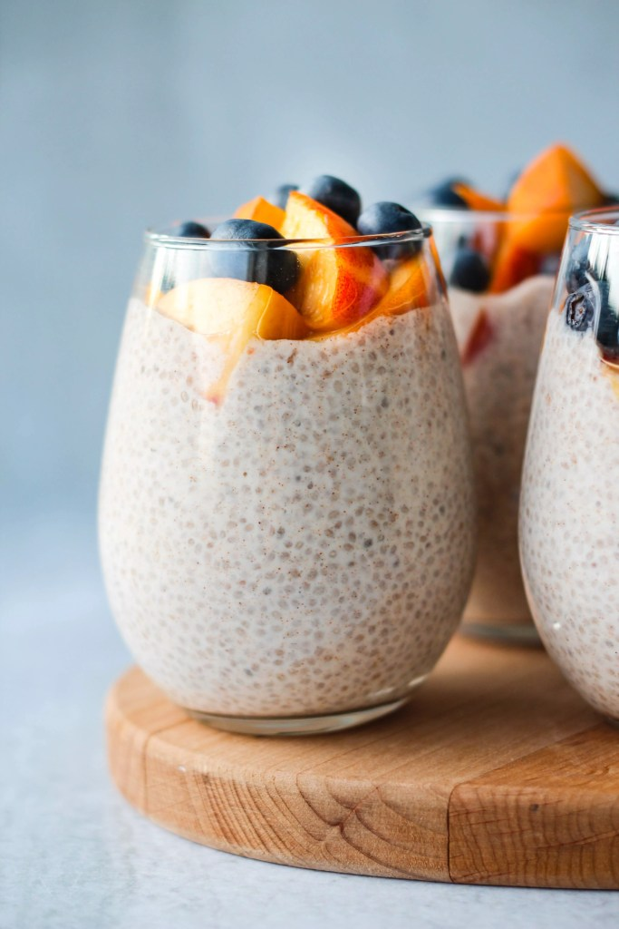 3 chia seed puddings topped with peaches and blueberries in glass jar