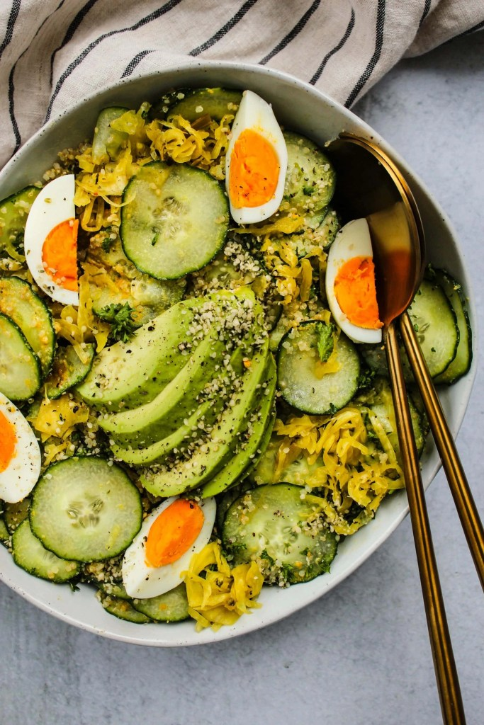 large white bowl with cucumber, avocado, quinoa, hard boiled eggs, sauerkraut salad and gold serving utensils