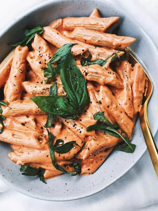 pasta with a vegan and dairy free cashew cream tomato sauce and fresh basil