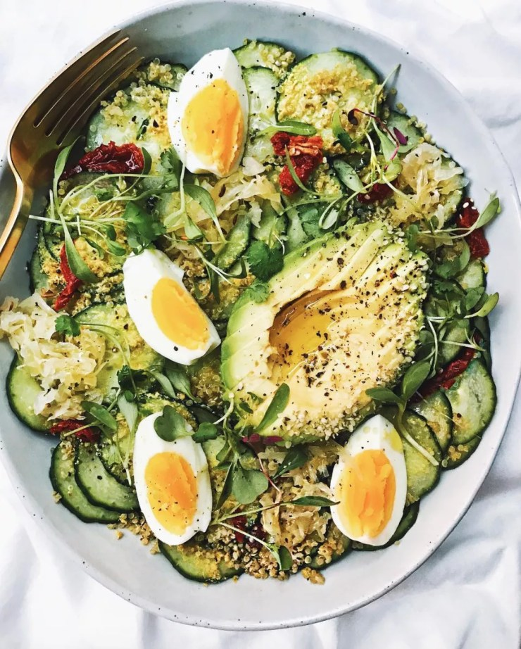 Bowl with cucumber salad, sauerkraut, avocado, hard boiled eggs, sundried tomatoes