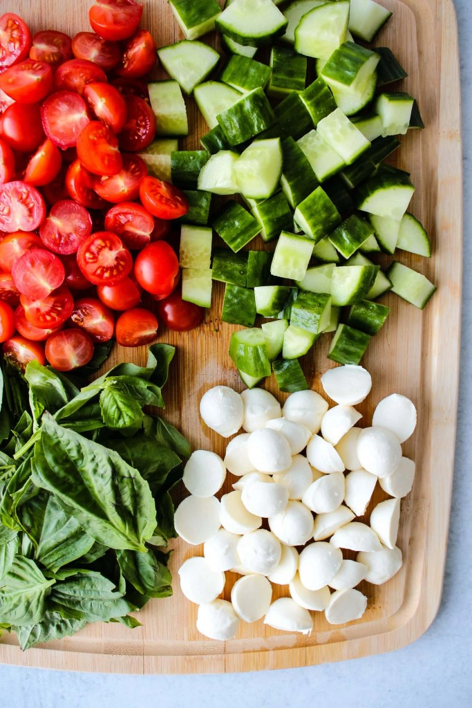 wooden cutting board with chopped cherry tomatoes, cucumbers, bocconcini cheese, and basil