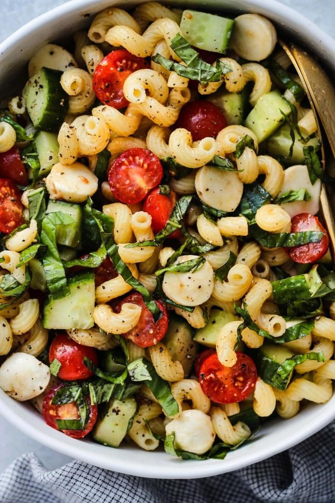 closeup shot of white bowl with cavatappi pasta, chopped cherry tomatoes, cucumbers, bocconcini, and basil