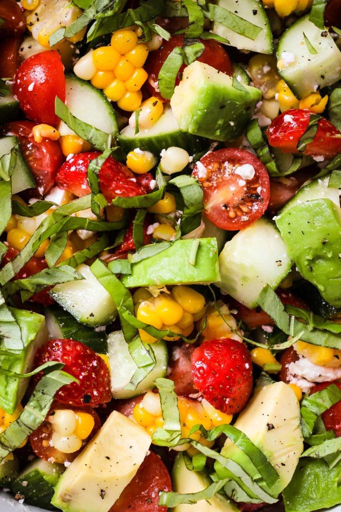 close up shot of summer salad with corn, tomato, avocado, strawberry, basil, feta
