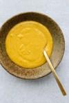 vegan miso tahini sauce in brown bowl with gold spoon