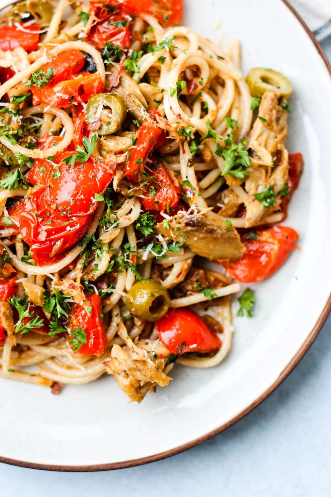 spaghetti with canned mackerel, red peppers, tomatoes, olives, and parsley on white plate