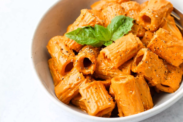 rigatoni pasta with roasted red pepper cashew cream sauce and basil in a white bowl