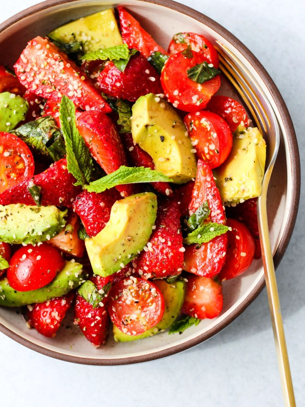 strawberry tomato avocado salad with mint, basil, balsamic, and hemp seeds in a white and brown bowl