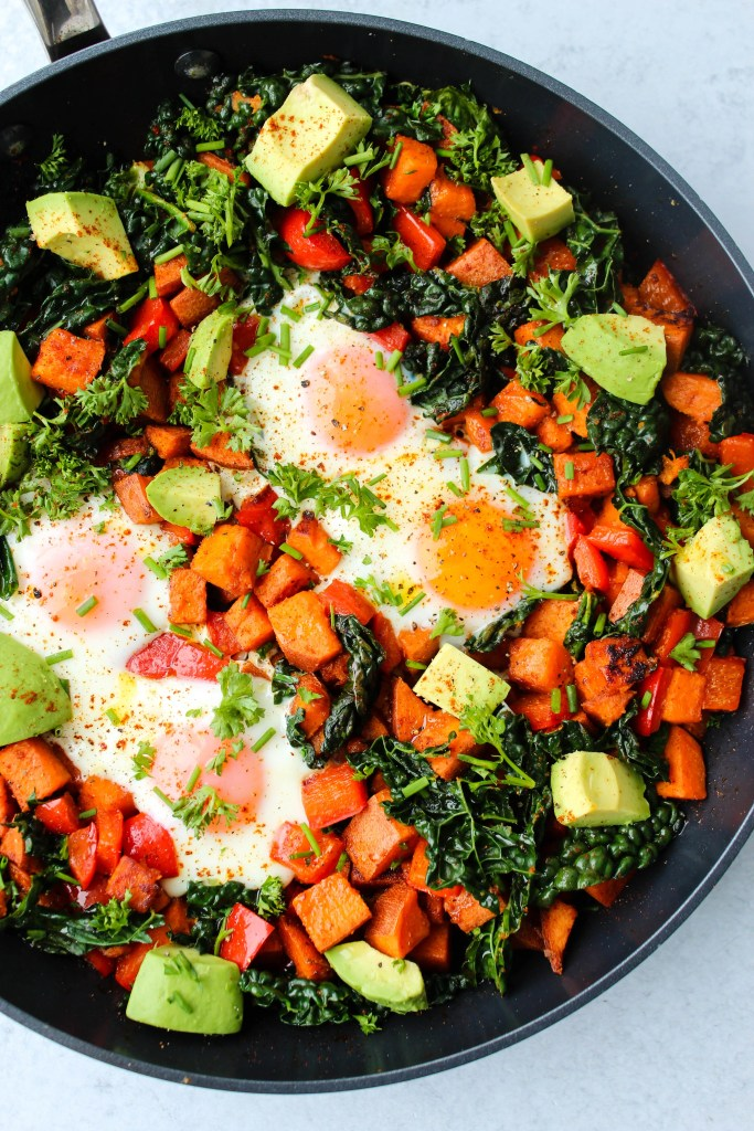 Overhead shot of sweet potato hash with red bell peppers, kale, avocado, and eggs in a black skillet