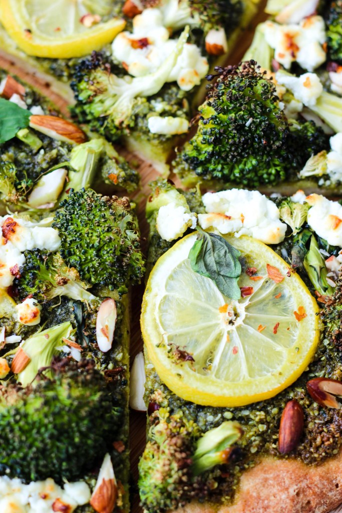 closeup of slices of homemade pizza with roasted broccoli, pesto, lemons, goat cheese crumbles, and almonds