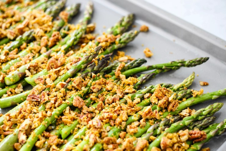 roasted asparagus topped with chopped pecan parmesan on a grey baking sheet