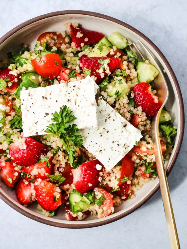 small bowl with strawberry quinoa tabbouleh salad and 2 pieces of feta cheese and gold fork
