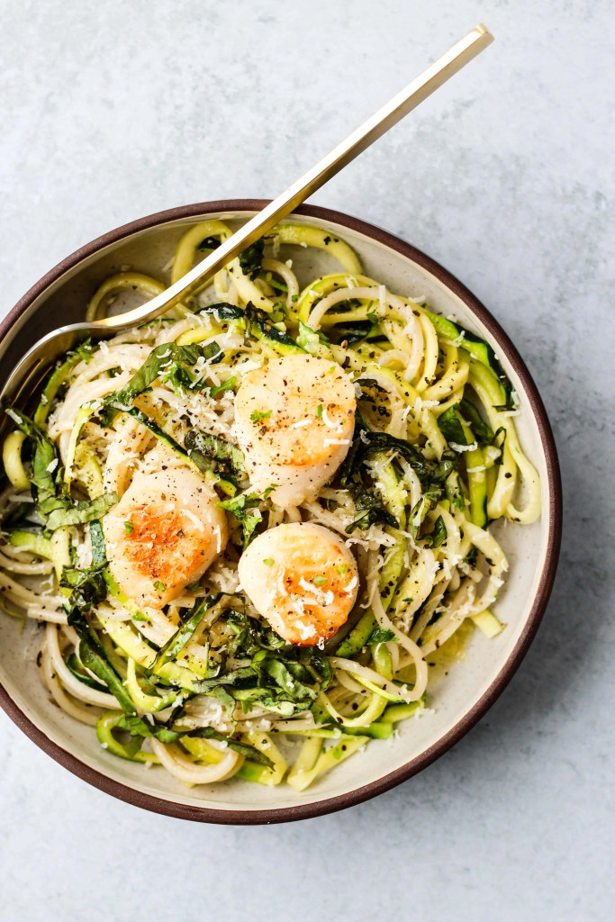 spaghetti and zucchini noodles topped with pan seared scallops in a brown and white bowl bowl