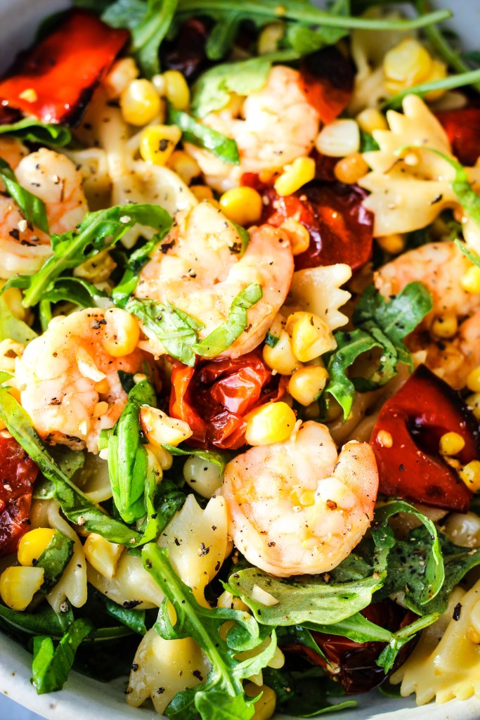 close up of roasted vegetable pasta salad with roasted red peppers, cherry tomatoes, corn, shrimp, and arugula