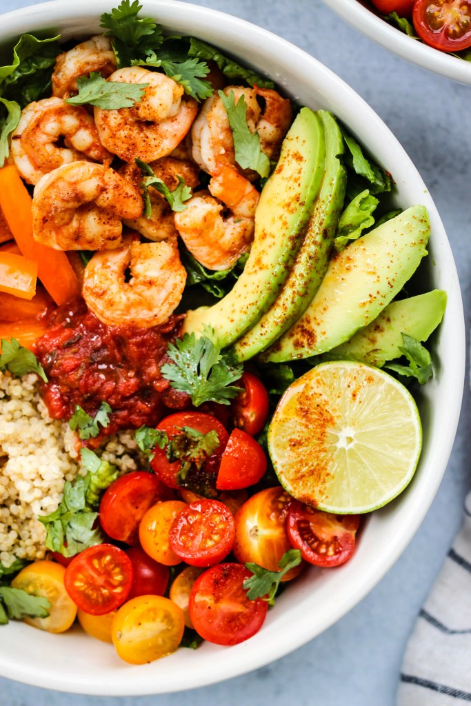 taco salad bowl with romaine lettuce, shrimp, avocado, bell peppers, tomatoes, quinoa, lime, cilantro