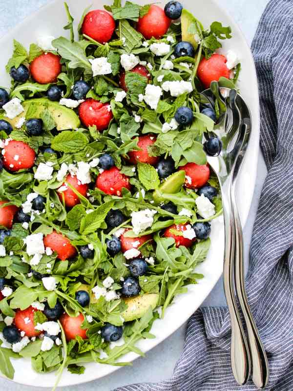 salad with arugula, watermelon, feta, blueberries, avocado on white plate