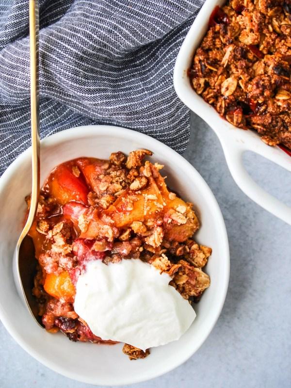 strawberry peach crisp in small white bowl with greek yogurt