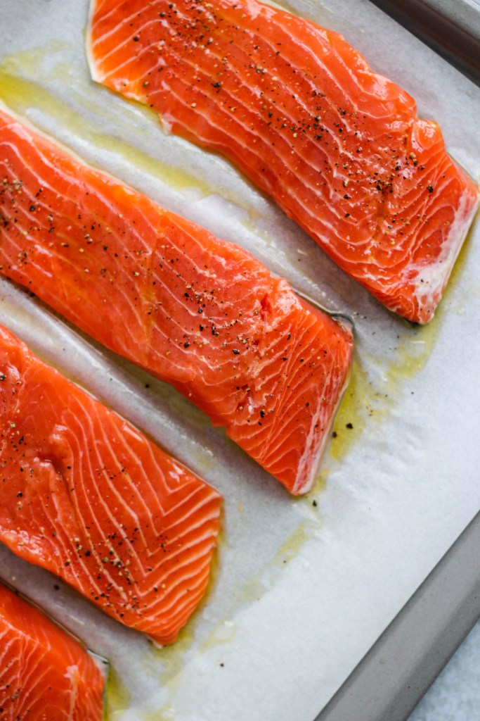 four salmon fillets on baking sheet
