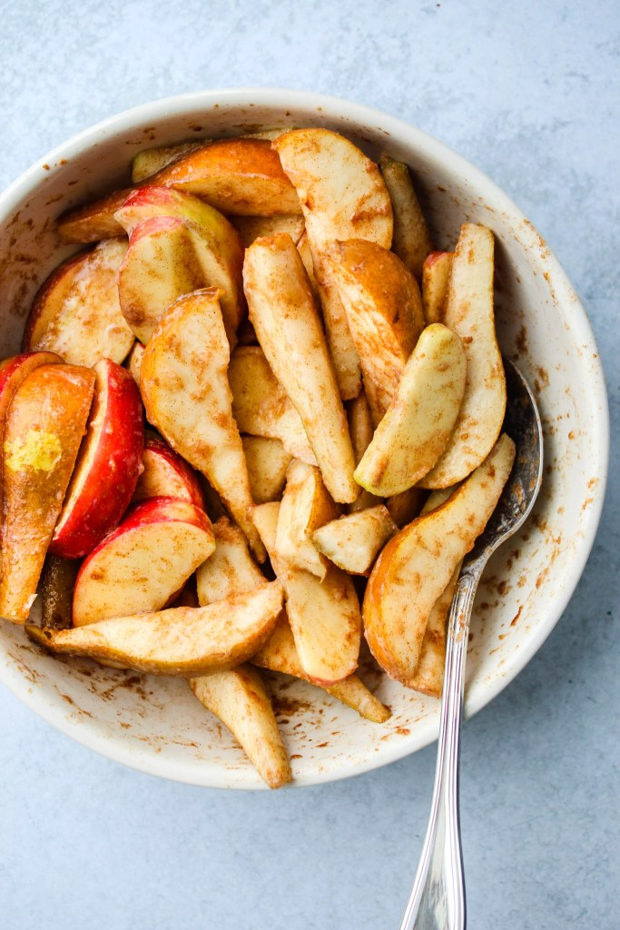 apple and pear slices tossed in spices in white mixing bowl