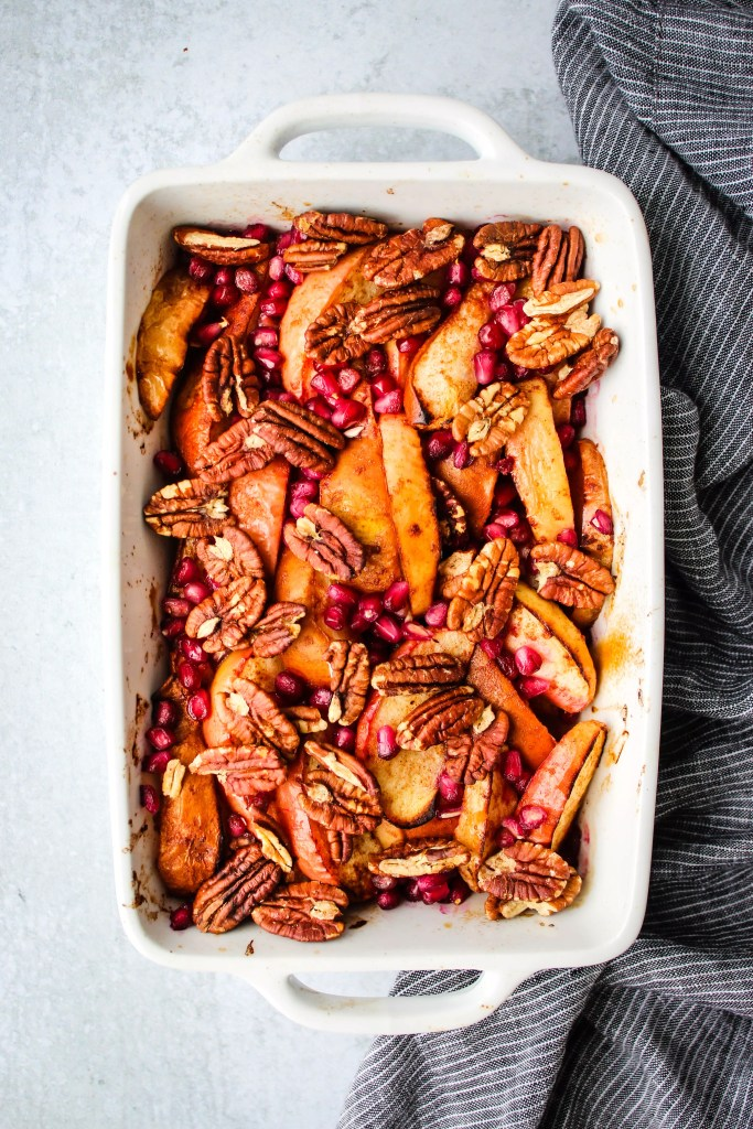apple, pear, pomegranate and pecan fruit bake in white baking dish