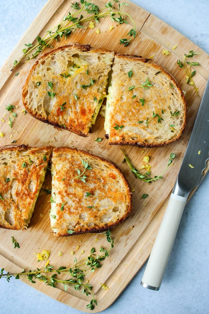two gourmet grilled cheese sandwiches slices on cutting board with fresh thyme