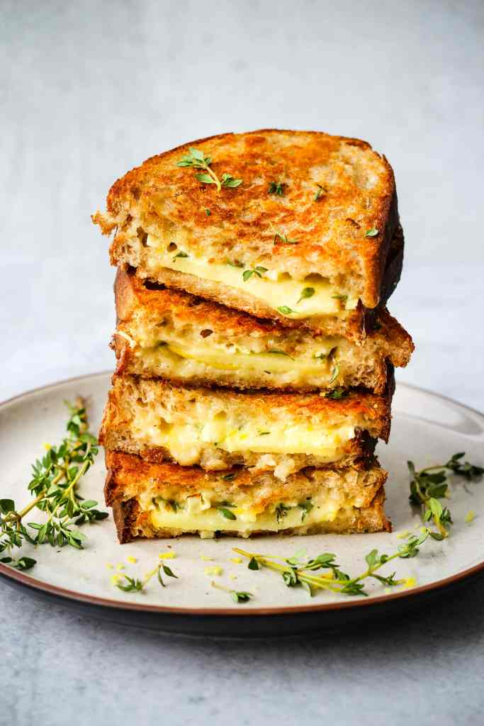 gourmet grilled cheese sandwich stacked on plate